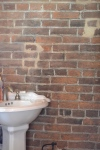 The half bath on the first floor was created from the old back stairway.  I love how the walls are the bare, 19th century brick.